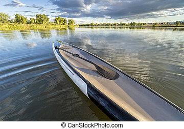 paddleboard with paddle on lake