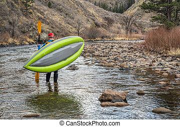 paddler carrying  inflatable whitewater kayak