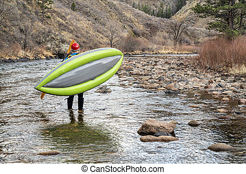 paddler carrying inflatable whitewater kayak on a shore of ...