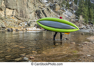 paddler carrying inflatable whitewater kayak - paddler...