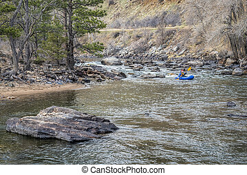 paddler in packraft on mountain river