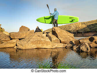 paddler with inflatable stand up paddleboard