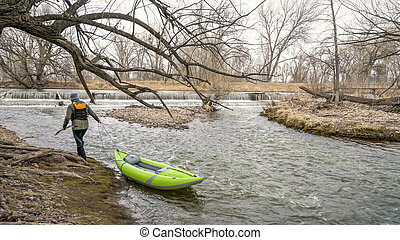 paddler with whitewater inflatable kayak