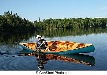 Paddling a canvas cedar canoe - Canoeist paddling a cedar ...