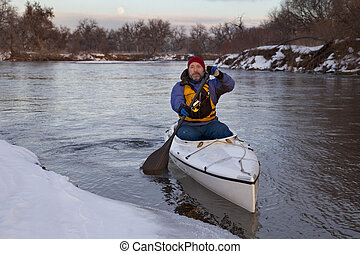 paddling canoe on a winter river - mature male paddling a ...