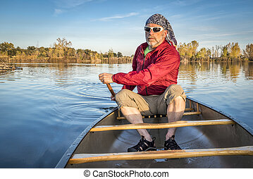 paddling canoe on calm lake - senior paddler enjoying ...