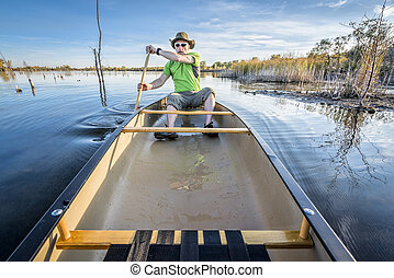 paddling canoe on calm lake - senior paddler paddling a ...