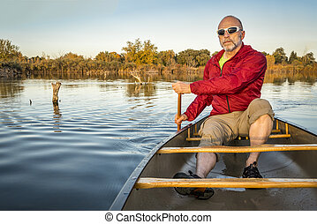 paddling canoe on calm lake