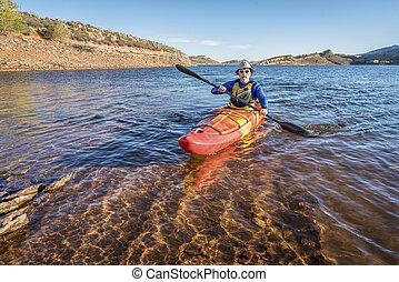 paddling kayak on mountain lake