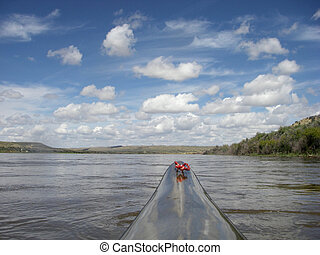 paddling racing kayak on river with desert landscape - ...