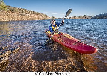 paddling river kayak on lake - senior male is paddling...