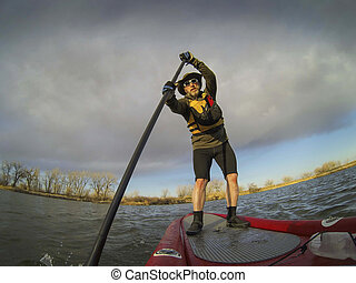 paddling stand up board - mature male paddler enjoying...