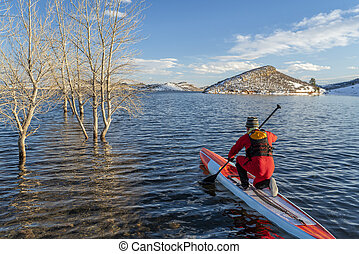 paddling stand up paddleboard in winter