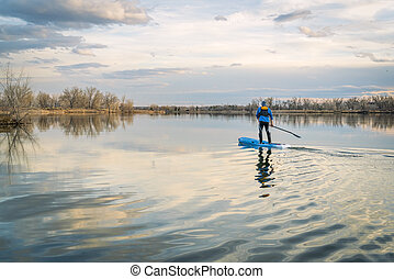Paddling stand up paddleboard on a calm lake