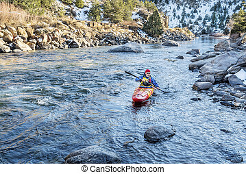 paddling whitewater kayak - senior kayaker in a whitewater...
