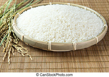 Paddy and rice grain over bamboo mat