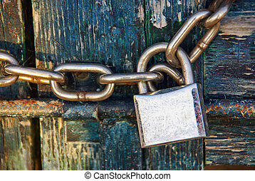 Padlock and Chain - Padlock closing an old wooden door with...