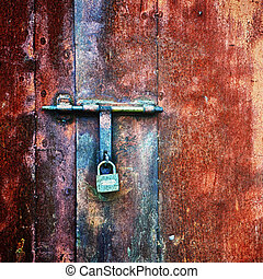 padlock on door of old rusted metal wall
