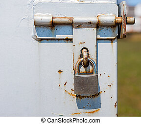 Padlock on partly rusted metal latch.