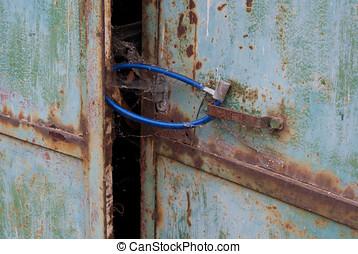Padlock on rusty door - Rusty metal door with cobwebs,...