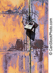 Padlock on rusty iron door - Old closed padlock on rusty...