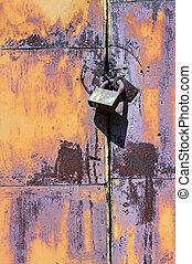 Padlock on rusty iron door