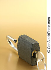 padlock - open padlock on a gold background with a key...