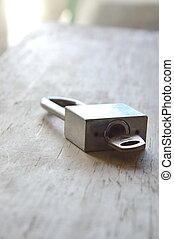 padlock unlocked on wooden board