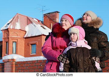 padre, madre e hija, posición, aire libre, en, invierno, cerca, casa, y, mirar, cielo, foco, en, niña