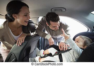 padres, asiento, bebé, coche, asegurar