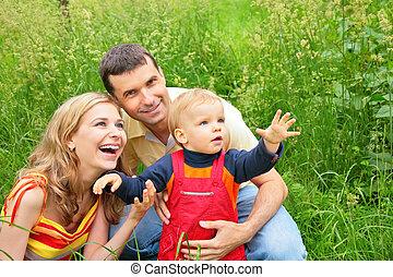 padres, con el niño, sentarse, en, pasto o césped, y, mirada, hacia arriba