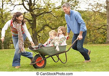 padres, dar, niños, paseo, en, carretilla