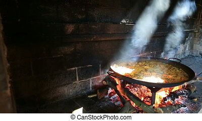 Paella and light - preparing large dish of paella with...