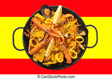 Spanish tradicional paella home-made composed of rice, and fresh seafood like clams, king prawns and squid rings is laid on spanish flag.