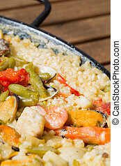 Paella rice with prawns cooked in a barbecue fire