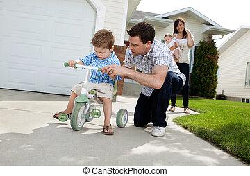 pai, ensinando, filho, montar, triciclo