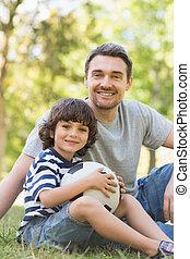 pai filho, com, futebol, sentar-se grama, inpark