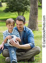 pai filho, sentando, com, bola, em, parque