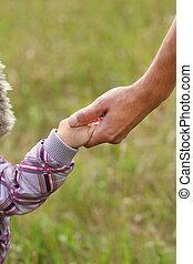 pai, segura, a, mão, de, um, criança pequena