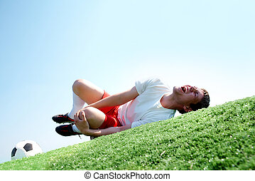 Image of soccer player lying down and shouting in pain