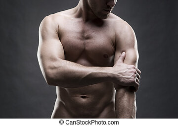 Pain in the elbow. Muscular male body. Handsome bodybuilder...