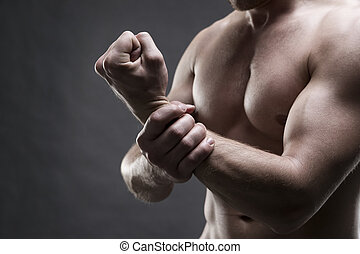 Pain in the hand. Muscular male body
