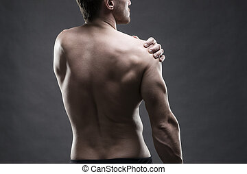 Pain in the shoulder. Muscular male body. Handsome bodybuilder posing on gray background. Low key close up studio shot