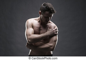 Pain in the shoulder. Muscular male body