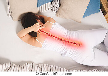 Pain in the spine, woman with backache at home, back injury