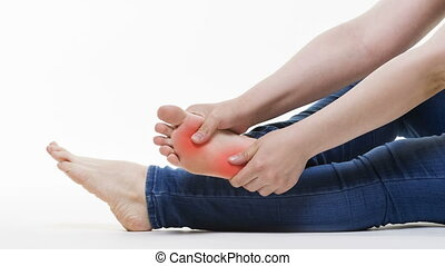 Pain in woman's legs, massage of female feet on white...