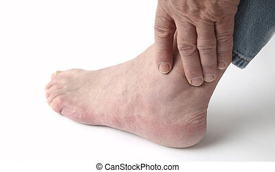 painful ankle - a man tends to his sore ankle
