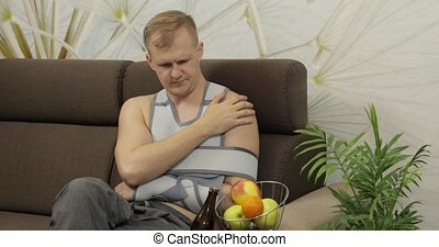 Man with shoulder injury. Painful, bored man with a broken arm wearing arm brace sitting on a sofa and drinks beer at home. Patient in a bandage for fixing of an elbow joint and a humeral belt