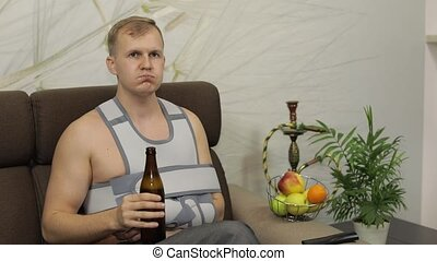 Man with shoulder injury. Painful, bored man with a broken arm wearing arm brace sitting on a sofa at home and drinks beer. Patient in a bandage for fixing of an elbow joint and a humeral belt