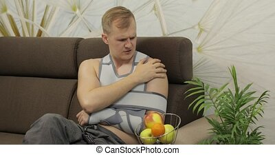 Man with shoulder injury. Painful, bored man with a broken arm wearing arm brace sitting on a sofa and watching TV at home. Patient in a bandage for fixing of an elbow joint and a humeral belt